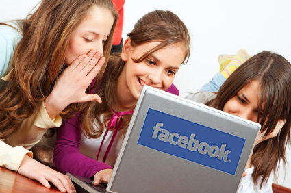 3 teenage girls with a laptop + facebook logo